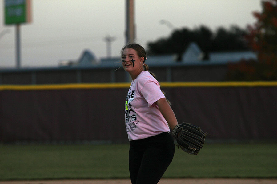 Senior softball captain Allie Barentine tosses the ball to another player while warming up for the Battle of the Bats rivalry game on Wednesday, Oct. 23.