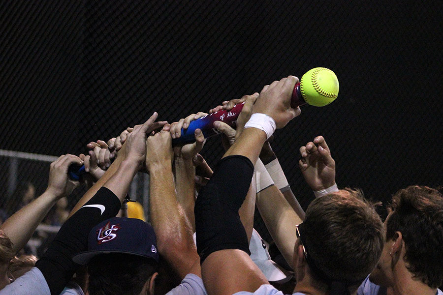 The baseball team holds up the bat following a victory at the Battle of the Bats game on Wednesday, Oct. 23.