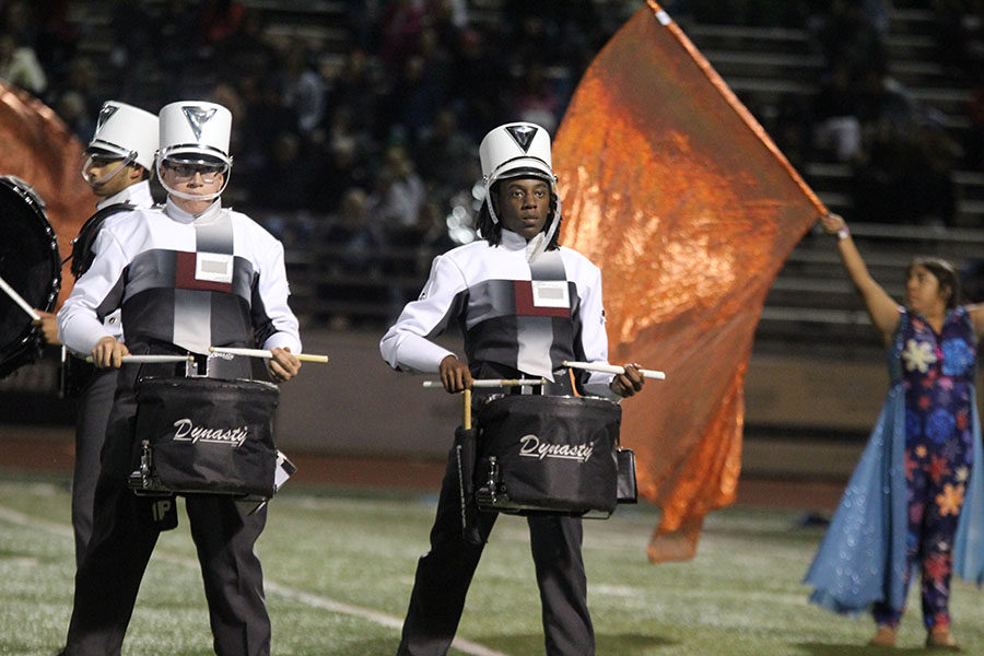 Junior Vince Carrion and sophomore Lawrence Williams stand in position before playing during the bands show A Cooler Shade of Winter.