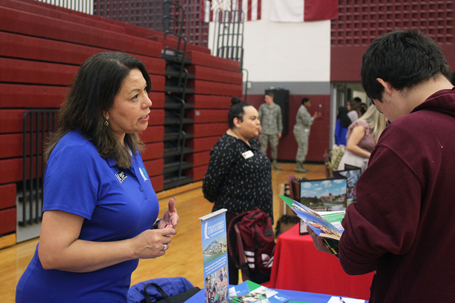 A Texas A&M Corpus Christi representative hands a brochure to a student, explaining the schools benefits.