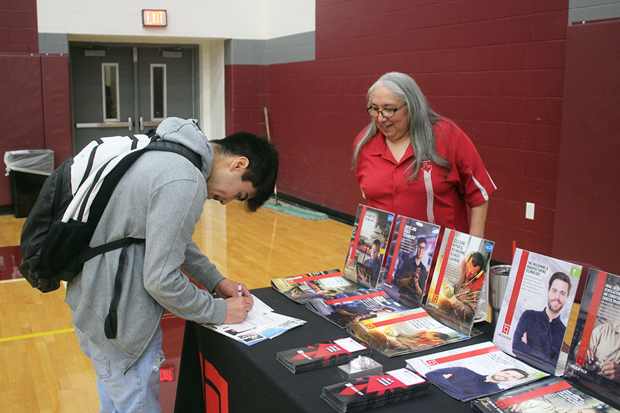 Giving a Lincoln Tech his contact information, a student happily learns about the college.