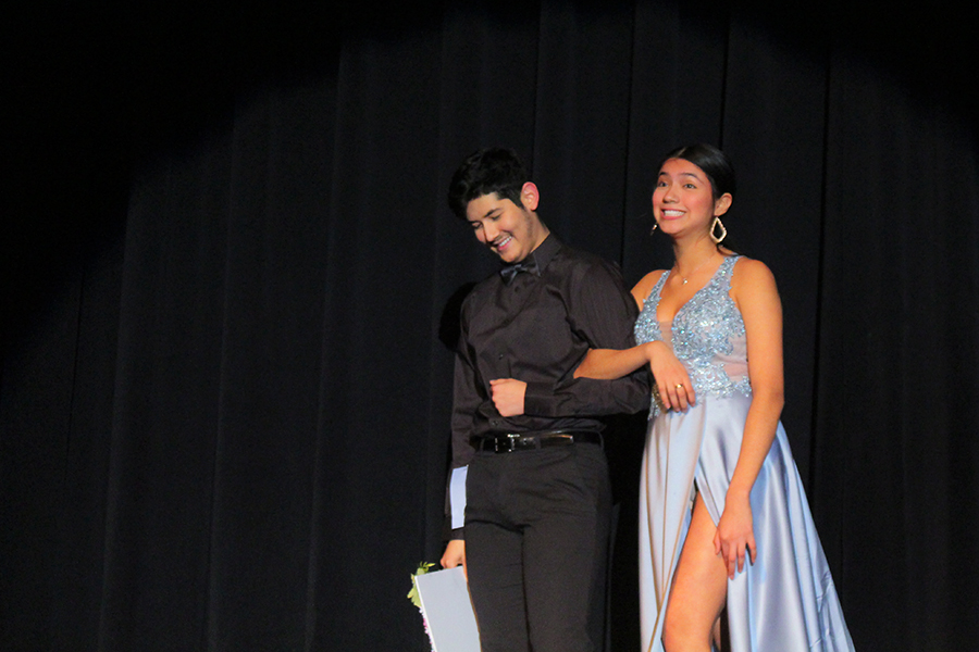 Senior Joshua Felix walks off stage with his girlfriend, senior Elizabeth Hernandez, after he asked her to prom during the pageant.