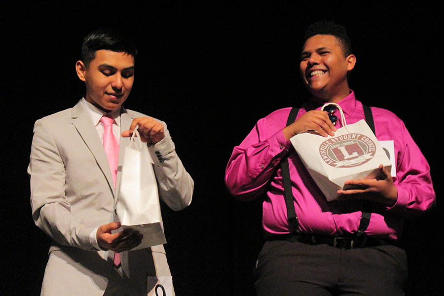 After given goody bags, seniors Roberto Martinez and Devante Hill smile and inspect their gifts.