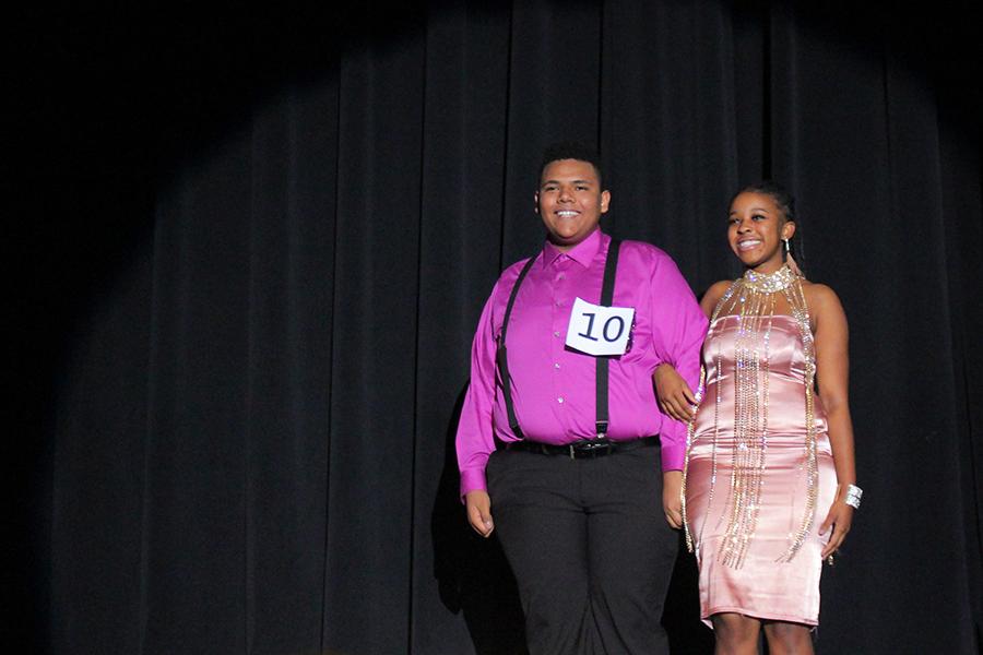 Senior Devante Hill walks on stage, escorted by senior Chaylyn Watkins.