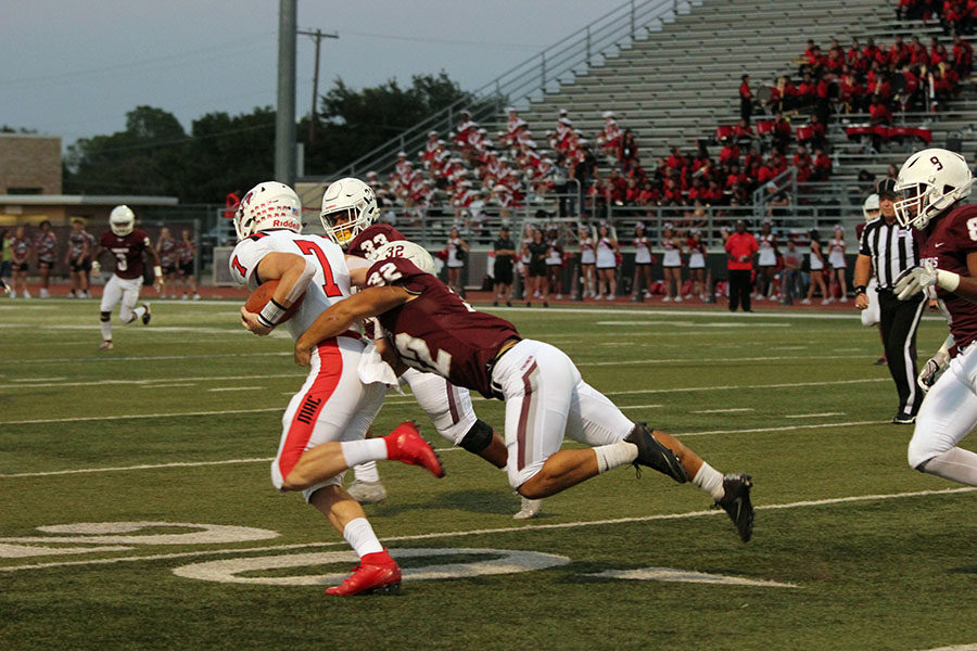 Senior defensive back Earl Barnes (32) takes out a MacArthur wide receiver.