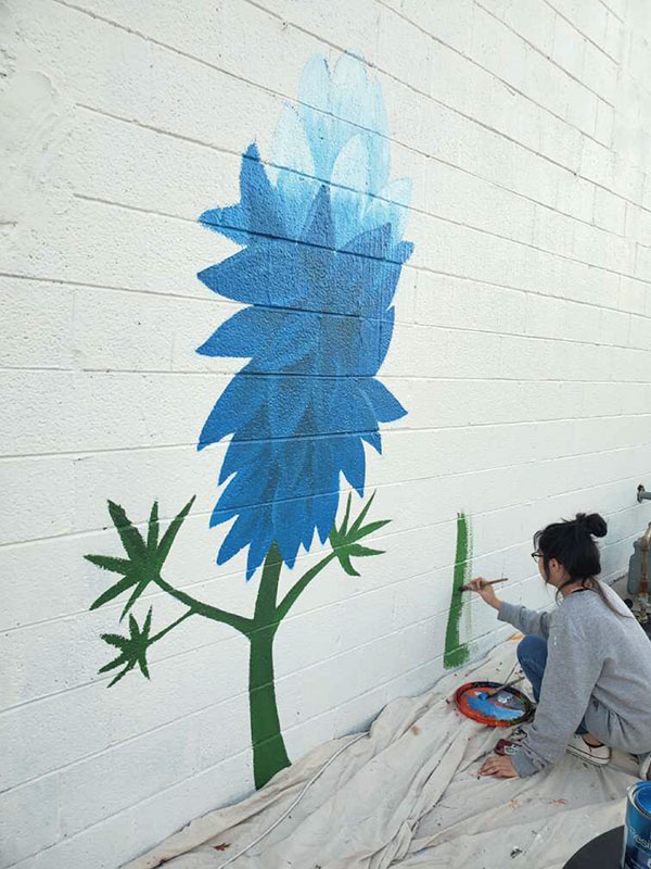 Montellano begins work on a second blue flower.