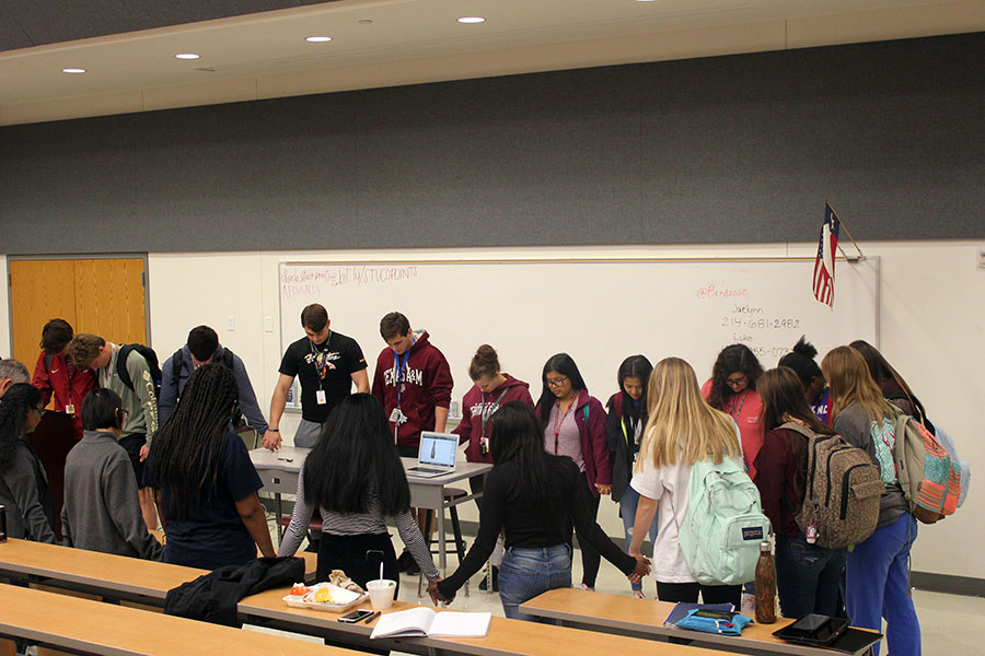 At the beginning of the kindness club meeting on Tuesday, Jan. 21, club members gather at the front of the lecture hall in prayer.