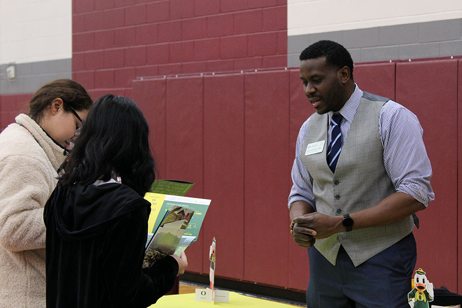A representative for the University of Oregon hands two students a packet of information.