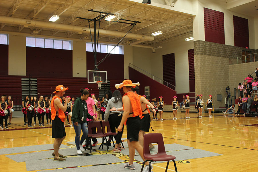 The boneheads play a game a of musical chairs with students.