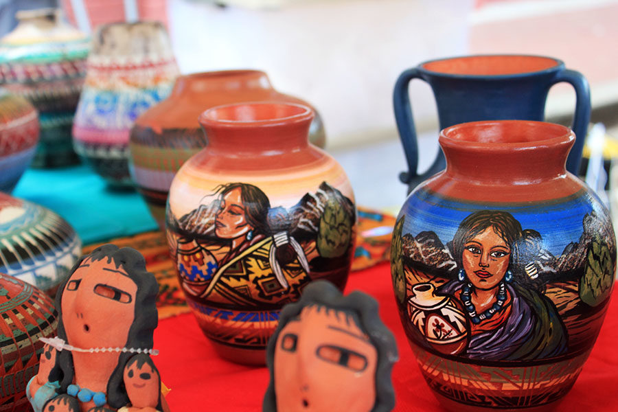 Handmade pots are displayed at a vendor's stand.