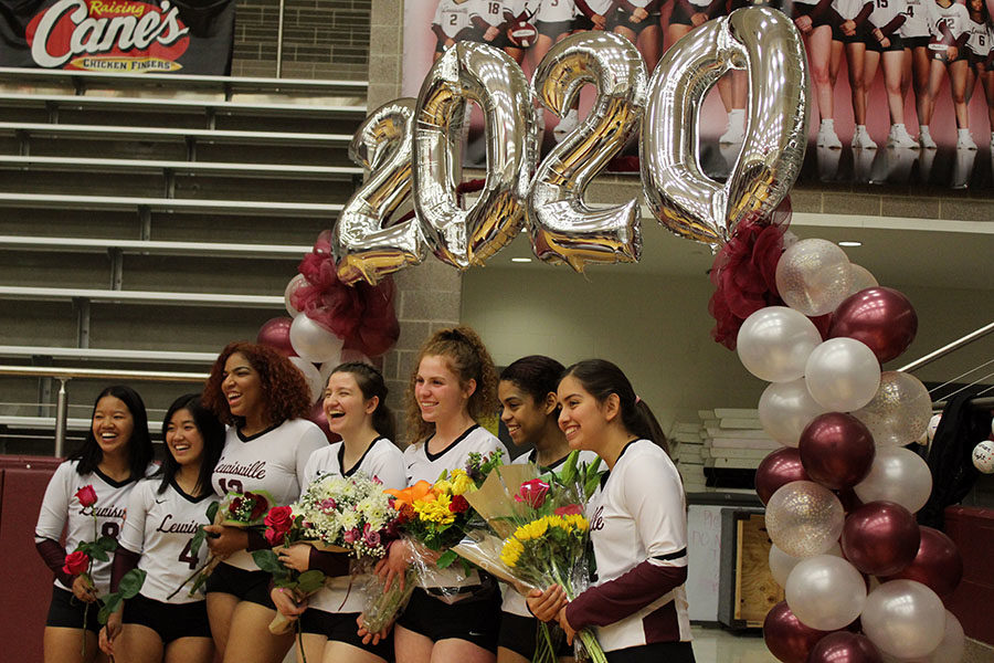 The varsity volleyball seniors pose together under a 2020 archway after being announced at the senior night game on Friday, Oct. 25.