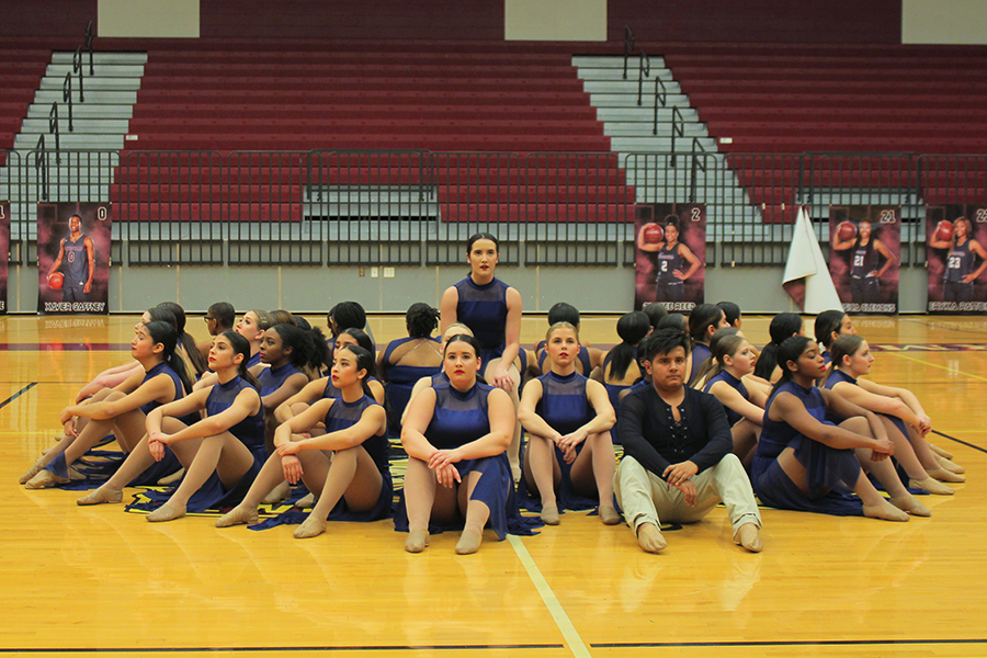Varsity Farmerettes start of the team contemporary dance, sitting around in a circle with senior captain Taylor Dill in the middle.