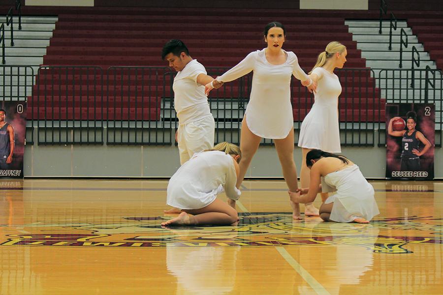 Senior and junior lieutenants hold onto senior captain Taylor Dill during the varsity officers modern dance.