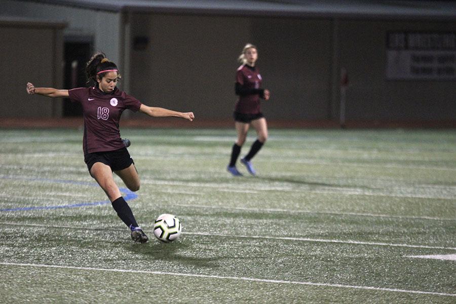 Junior Kara Papadimitrio (18) kicks the ball.