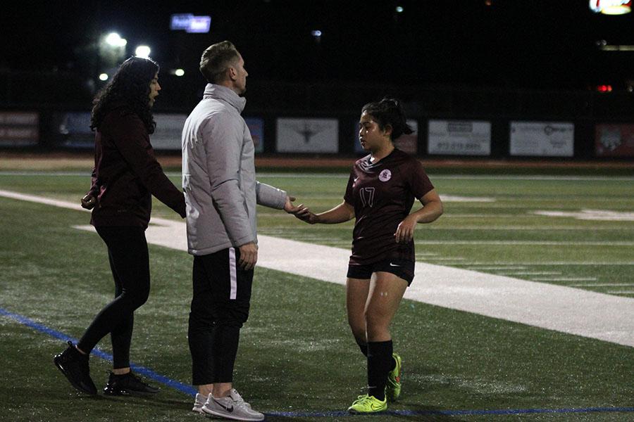 Head coach Jason Gaglione gives junior Victoria Sibounheuang (17) a high five as she runs off the field.