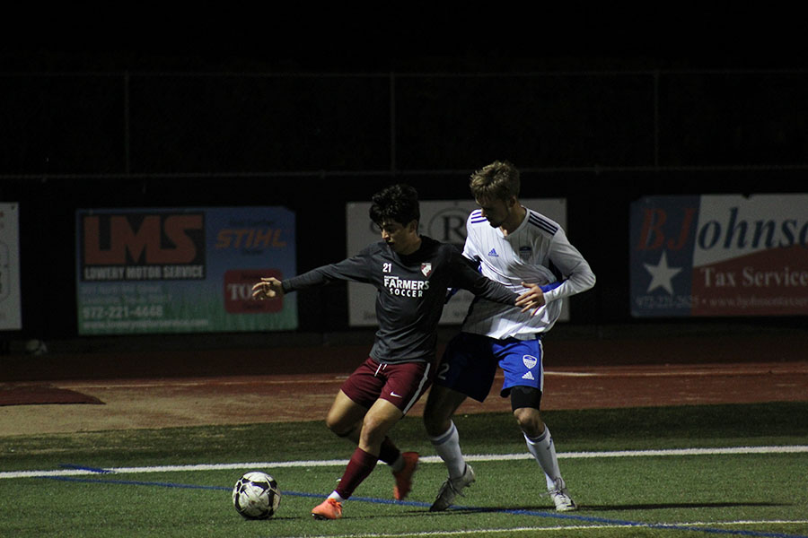 Senior captain Ethan Carbajal (21) defends the ball, searching for an opening to pass.
