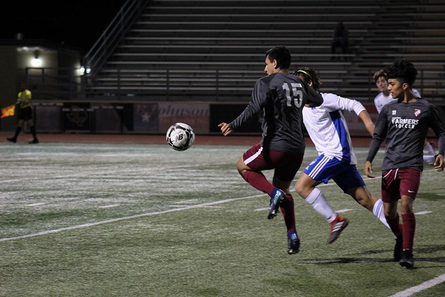 Senior Brandon Jimenez (15) kicks the ball away from a Hebron player.