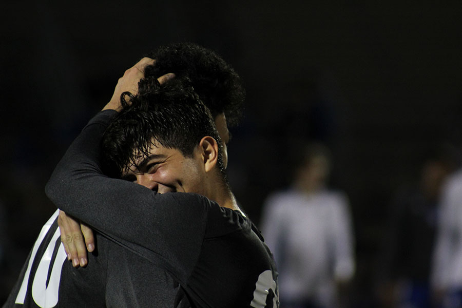 Senior captain Ethan Carbajal (21) and senior Fernando Gonzalez (10) hug to celebrate the 1-0 win against Hebron.