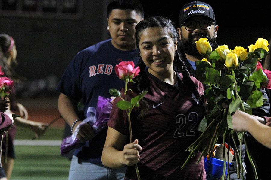 Walking in front of her family, senior captain Krisalin Salgado receives roses from her teammates.