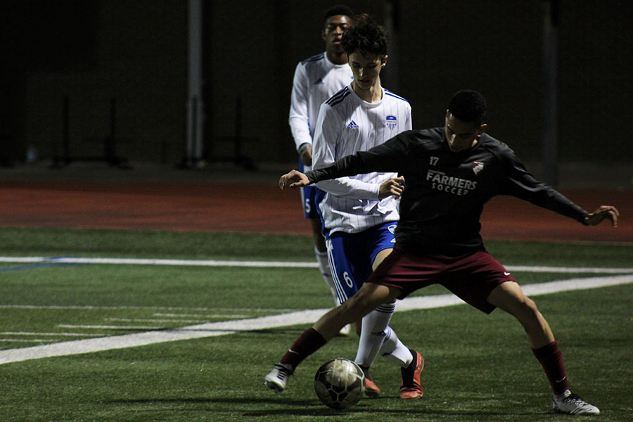 Senior Daniel Pineda (17) guards the ball from a Hebron player.