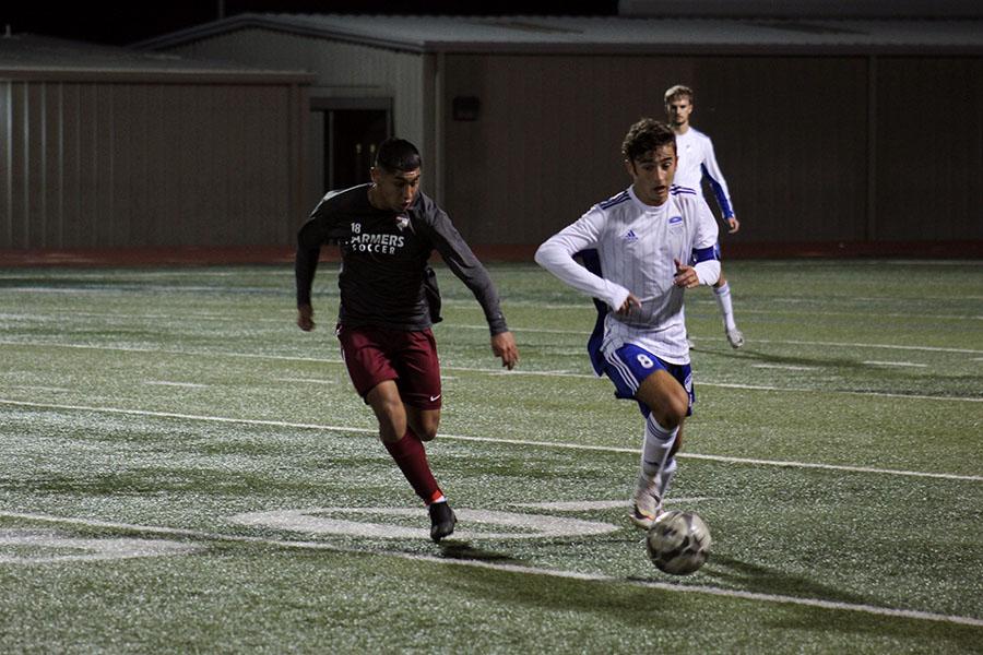 Senior Kobe Soto (18) races a Hebron player to the ball.
