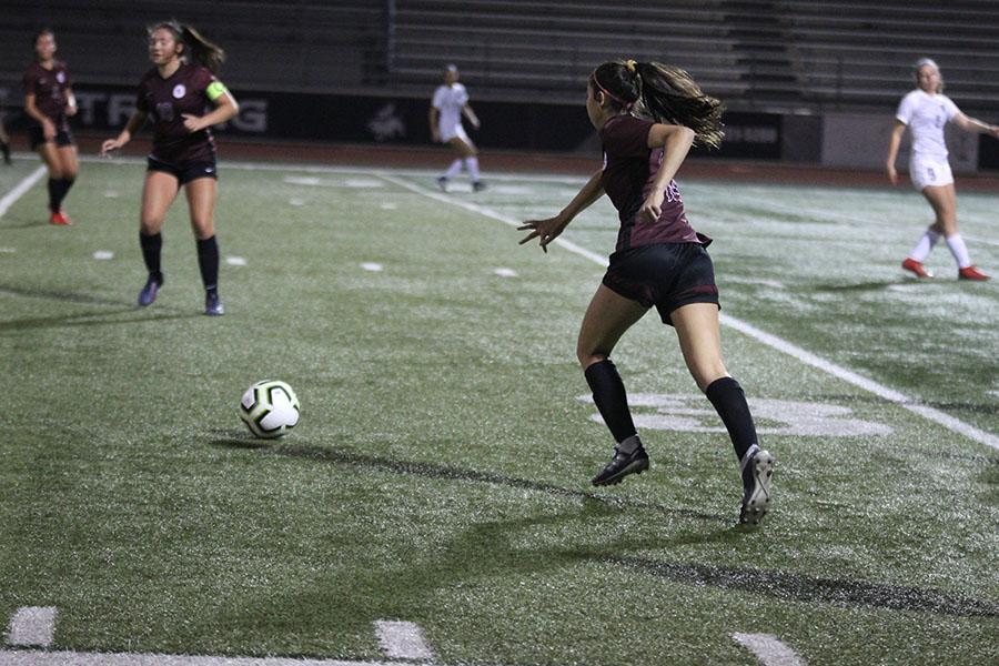 Junior Kara Papadimitrio (18) runs to kick the ball.