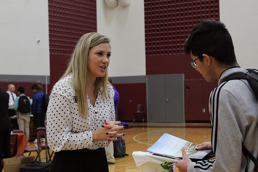 A Texas Tech representative discusses a flyer of information with a student.