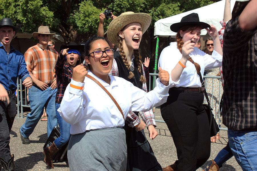 A group of theater students yell in excitement as they walk in the parade.