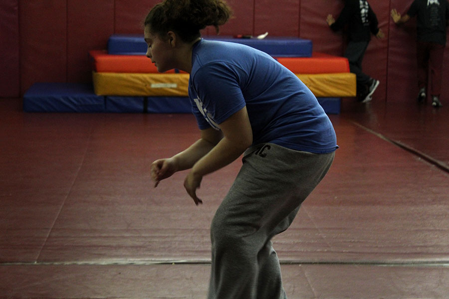Senior captain Charity Castañeda practices dodging a tackle during fourth period wrestling practice.