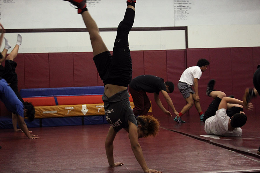 -- does a handstand as part of the warm-up during fourth period practice on Thursday, Nov. 21.
