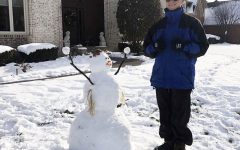 Senior Shawn McConnell takes a picture of the snowman he built during the winter storm on Feb. 15.