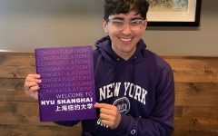 Senior Luis Alvarado poses with his acceptance letter to NYU Shanghai.